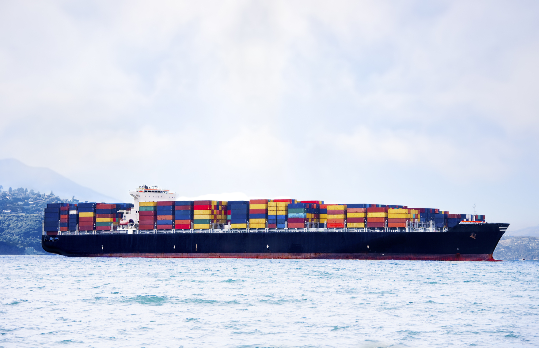 stockfresh_1384280_large-cargo-ship-in-water-carrying-colorful-shipping-containers_sizeM